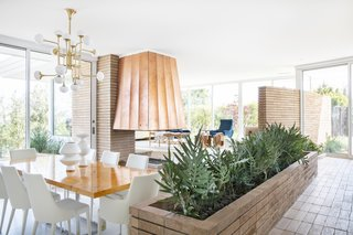 The renovation restored the built-in brick planter and exchanged the carpeting for sleek white terrazzo floors.