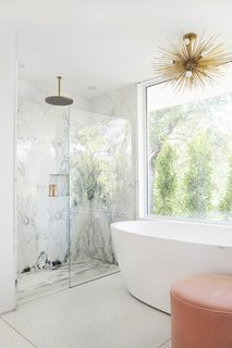 The marble continues into the shower, while a freestanding tub is set up to take in the view.