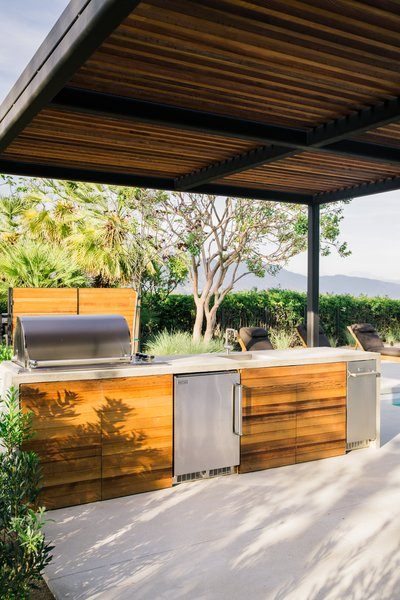 The outdoor kitchen features Fire Magic outdoor appliances.