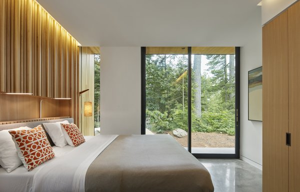 The wood wall cladding continues into the bedrooms, which remain private while also accessing the outdoors.