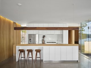 The kitchen scheme features banks of white, flat-front cabinets for serene contrast with the wood palette.