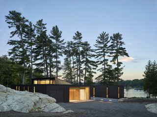 The low-lying home, completed in 2018, sits behind a stand of pine trees just steps from the water.