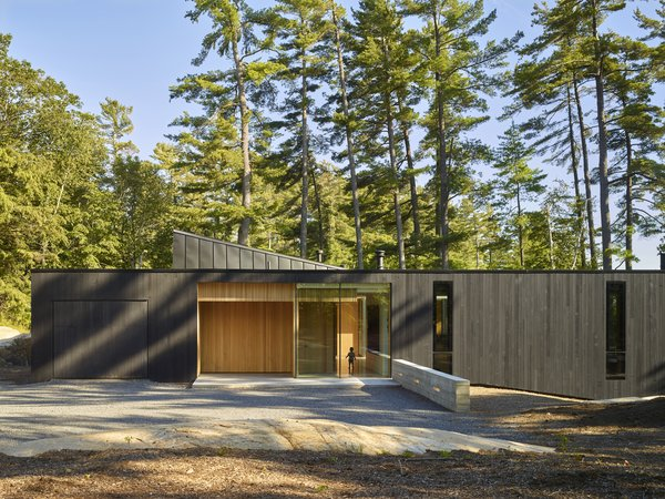 "The dark exterior wood cladding ensures the home blends more seamlessly with the site, while the flat roof is meant to recall ""midcentury precedents,"" said the architects. The ""sharkfin clerestory roof"" feature transmits light into interior rooms."