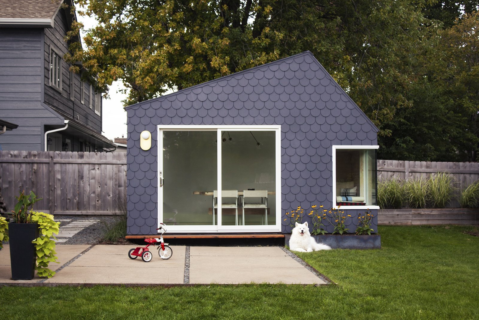 "Exterior, Sawtooth RoofLine, Tiny Home Building Type, Metal Roof Material, and Concrete Siding Material The couple finished the exterior siding with shingles made of Hardie board and painted a deep purple. ""We wanted an exterior cladding that was durable, low-maintenance, and relatively DIY-friendly,  Best Photos from Budget Breakdown: A Creative Couple in Minneapolis Build a Multipurpose Backyard Studio For $18K"