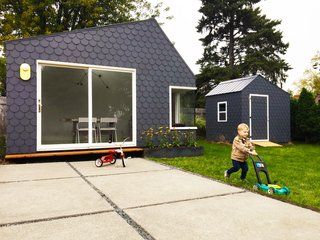 "The couple finished the exterior siding with shingles made of Hardie board and painted a deep purple. ""We wanted an exterior cladding that was durable, low-maintenance, and relatively DIY-friendly,"" says Michael. ""When looking at our options at the local hardware store, the fish-scale shape popped because it was unique, quirky, and not super serious—and yet could create a contemporary look through uniformly using it with woven corners and minimal detailing."""