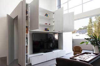 "A glimpse of the storage capabilities now provided by the cabinet room. ""The loft came with little storage,"" says Knayzeh. ""We needed to have the ability to hide general mess when we have company."" Integrated cabinets in the walls of the room now provide a coat closet, document filing, and space for Knayzeh's book collection around the perimeter."