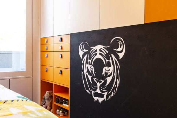 The room's interior scheme is more playful, befitting a child. A chalkboard backs the TV niche and is bordered by bright orange cabinetry sized for children's clothes.