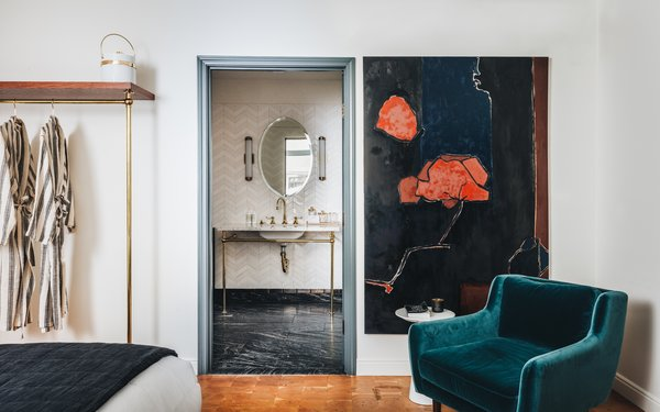 Large-scale artwork makes a statement throughout the hotel, and the collection includes paintings by Parquet Courts singer Andrew Savage. The bathroom juxtaposes chevron wall tile with a traditionally appointed sink and luxe black stone floor.
