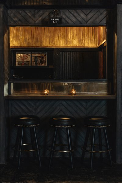 The interior features brass details, dark wood chevron walls, and tufted leather seating.
