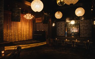 Gold velvet curtains line the stage, which features a DJ or live music nightly, in a selection curated by Justin Gage of Aquarium Drunkard. Gilt chandeliers and textured walls complete the scheme.