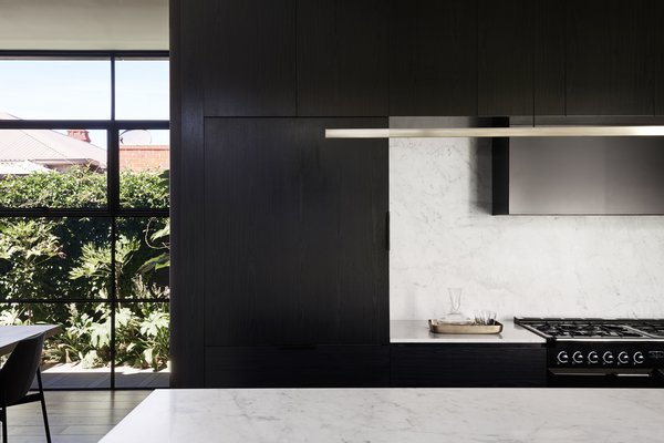 """The kitchen was conceived as a """"pod"""" that subtly separates the living and dining areas. The pendant light over the Carrara marble island is by Archier."""