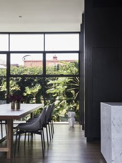 The dining room overlooks the smaller southern courtyard, with chairs by Meizai and a sculpture by Den Holm. The floors are engineered oak throughout.