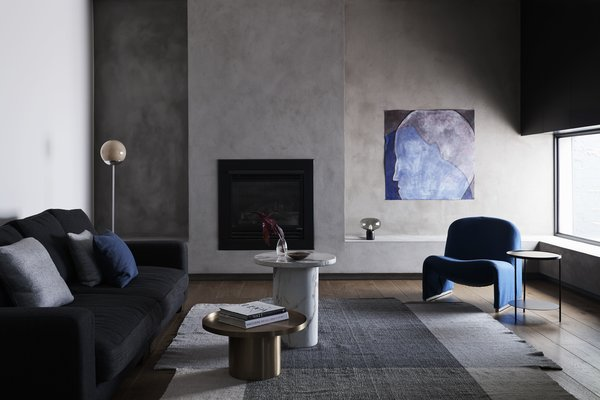 """The living room received windows with deep reveals and a natural sand cement render to one wall to impart a """"moodier"""" vibe."""
