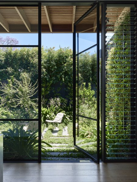 A wall of glazing across from the kitchen pod connects to a centrally located courtyard, with landscaping by Eckersley Garden Architecture.