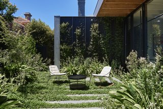 "The courtyard lets the reimagined addition live as a ""modernist ruin,"" with vines encouraged to grow and further blur the boundary between inside and out. The outdoor table and chairs are by Tait."