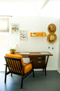 The office niche features a desk from Joybird and a citrus-colored metal wall shelf by New Made LA.