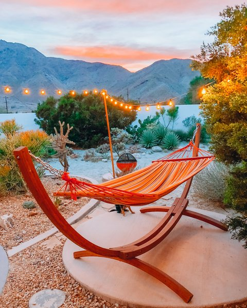 A striped hammock is perfectly placed for relaxing and taking in the sunset.