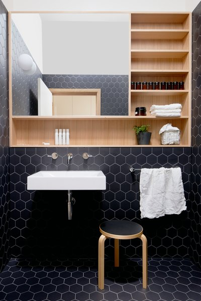 "The powder room is a retreat from the main living areas. The firm set off the Victorian ash storage and mirror unit by surrounding it with black hexagon tile. A ""sky tunnel"" in the ceiling floods the room with natural light."