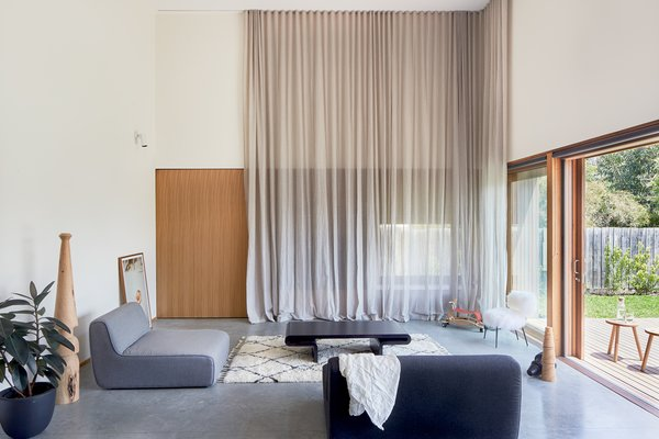 A floor-to-ceiling curtain is set up to provide additional privacy and light modulation when needed.