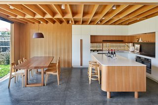 "The kitchen got a place of pride in the addition, as the family loves to cook, and the lowered ceiling differentiates it from the adjacent living area. The custom island received a rounded corner that echoes the entry. ""The unusually shaped island bench responds to the geometry of the external glazing, which was in turn angled to respond to exterior views,"" says the firm. Circular legs on the island gives it a furniture quality and imparts a ""lightness"" to the large piece. The lattice over the window provides dappled, natural light and will eventually be covered in vines."