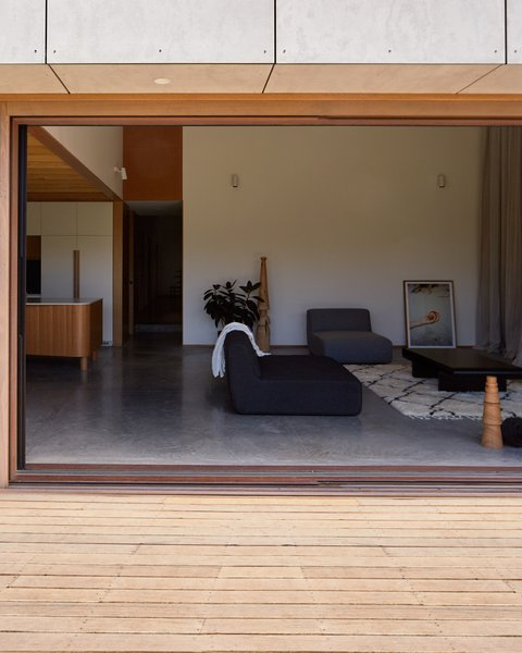 """The house was designed with passive heating and cooling strategies in mind, which are so successful that there is no air conditioning. The thickened wall over the north-facing glass forms an eave, which helps to modulate incoming sunlight in the summer. """"In winter, the sun can penetrate well inside the living and dining rooms, warming the floor slab,"""" says the firm. Additionally, """"the double height of the living space provides stack ventilation, with an operable highlight window naturally drawing hot air up and out."""" Cross-breezes are encouraged by effective window and door placement."""
