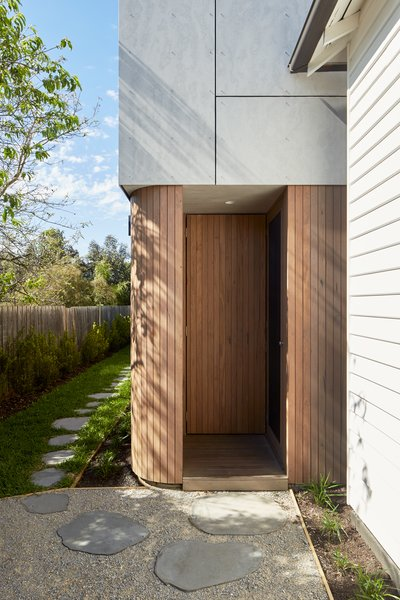 """Throughout Thornbury House, Olaver Architecture was deliberate about applying """"minor alterations to simple forms,"""" to make the so-called """"box"""" addition feel more special. Starting at the entry, a timber-clad, curved corner creates flow."""