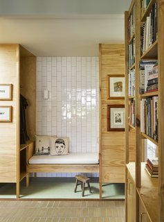 A purposeful nook for storing coats and taking off shoes is lined with vertical subway tile. The brick floor elegantly meets the pistachio green tile floor, which helps to define the alcove from the main space.