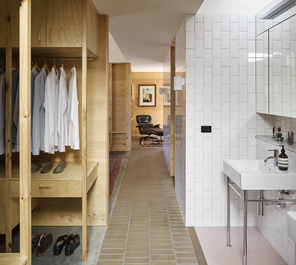 A private study connected to the master bedroom is glimpsed down a corridor. The bathroom sinks occupy their own tiled niche.