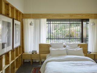 This bedroom, as well as two private studies, received the same built-in furniture treatment. Exposed studs further enable those built-in elements to blend with the framework of the house.