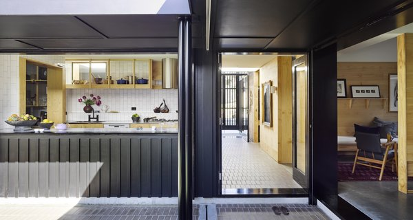 """This view shows how the interior and exterior passageways intersect, as well as the relationship between the courtyard and the street. The architects sought to ensure privacy, so the homeowners can enjoy their garden undisturbed. """"Suburban houses need to respond to the rigors of privacy and security, amongst others demands,"""" says the firm. """"Day-to-day rituals and routines may be embellished by natural light, social relationships, and a proximity to nature. The making of a home is about enclosure, comfort, and pleasure."""""""