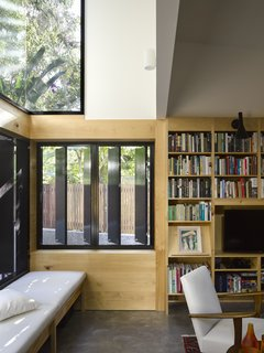 Light cascades onto the window seat from glazing placed high on the wall.