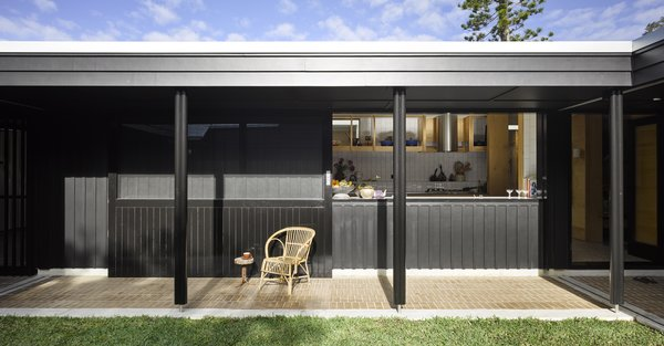 A large opening in the kitchen lets it overlook the courtyard, and a covered walkway provides easy circulation and protection from the elements to further encourage inhabitants to engage with the setting.