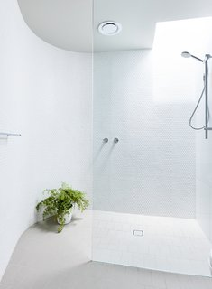 The upper level bathroom is tucked inside the curved central core, indicated by the rounded wall clad in white penny tile.