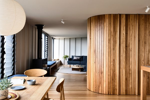 Upstairs, a curved wall clad in Silvertop ash joinery gently separates the living room from the kitchen and dining area. On the kitchen side, the wall hides the pantry and fridge.
