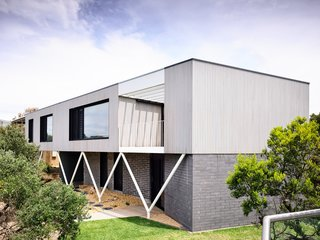 """On the exterior of the two-story beach house, much of the original brickwork was kept, and the new addition at ground level is faced in smooth, concrete blocks. The architects wrapped the upper floor in a new """"timber skin"""" of Silvertop ash shiplap with a Grey Mist finish, then inserted V-shaped steel supports that reference historic, Australian beach houses in the area."""