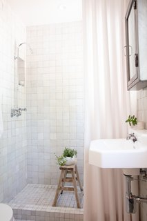 In the guest bath, white zellige tiles from Clé line the walls and floors and boast a myriad of undertones, from gray to cream to pink, which sync with the rest of the house.