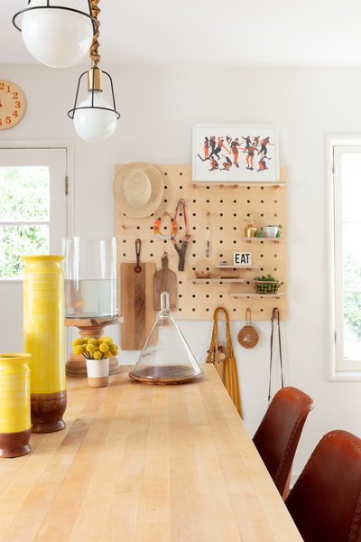"""The kitchen received a light """"punch-up,"""" including this wall-mounted pegboard shelving system."""