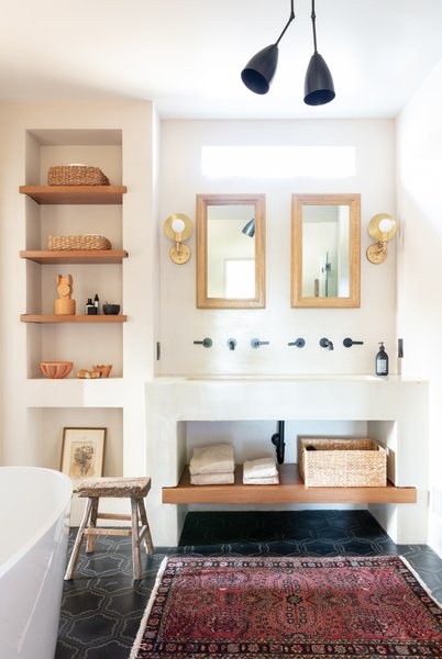 """The master bath also received a new materials palette, including tile from Mosaic House, lights from Apparatus and Workstead, and tadelakt plaster walls and ceiling, which the designers say """"feel simultaneously consistent with other home elements, yet fresh and forward."""""""