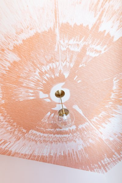 A unique spin art design in peach livens up the ceiling in a teen's room.