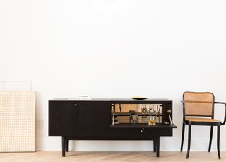 A drop-down door in Coil + Drift's Rex credenza reveals a mirrored compartment ideal for barware display and storage.