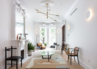 The firm also widened the room and raised the ceilings. A coat of bright white paint modernizes the historic details.