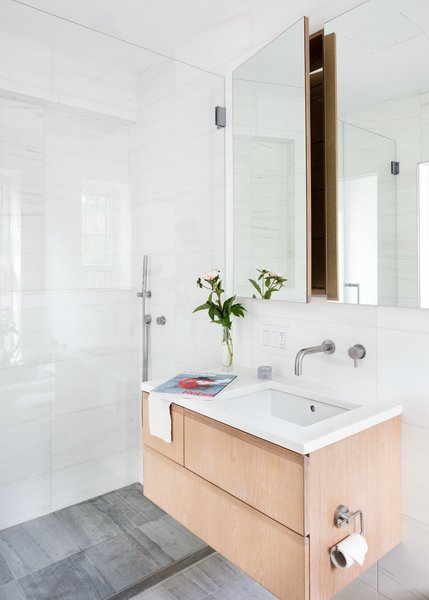 A custom white oak vanity and medicine cabinet adorn marble walls in the bathroom.