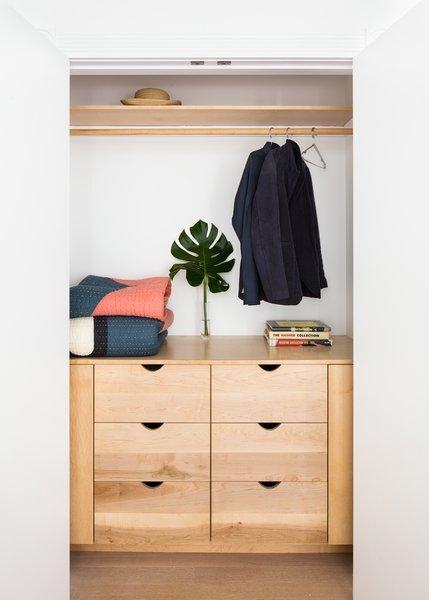 A closet features sleek built-in storage.