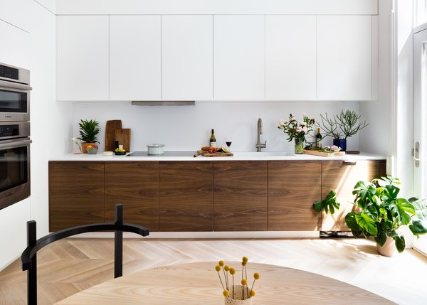 Hatchet Design Build took a more modern approach with the kitchen while still drawing from the traditional palette. The grain-matched walnut kitchen cabinets echo the walnut pocket doors elsewhere.