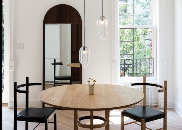 In the dining room, a Cirrus double pendant hangs over a Soren dining set, both from Coil + Drift.