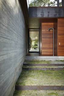 Teak surrounds a minimalist outdoor shower.