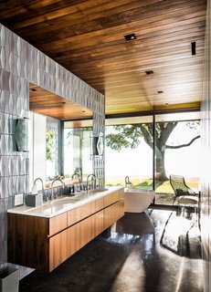 A wall of dimensional Heath Ceramics tile—the Bowtie and Diamond mixed—backs a teak and quartz floating vanity.