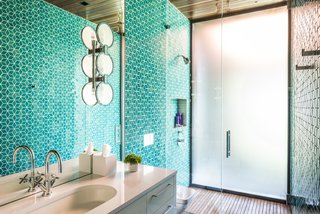 Another bathroom sports the Dwell Little Diamond tile in the Tropics Blue Crackle glaze from Heath Ceramics. The shower floor is also teak.