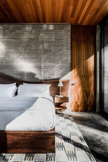 In a bedroom, the walnut live-edge bed is a custom design from Emily Summers Design Associates.