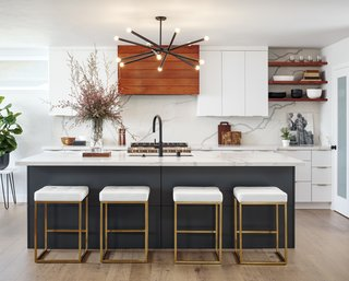 By removing walls and a counter peninsula jutting into the room, interior designer Corine Maggio was able to create enough space for a generous island. The stove wall is a fitting focal point with a hood vent accented in tigerwood and a quartz slab backsplash. Black and brass accents, including the Renwil chandelier and Nuevo Living stools, are a theme throughout.